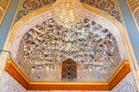 Shiraz, Iran - 29 October, 2018: Amazing details of Persian interior of the Shah Cheragh Mosque and Mausoleum. Shimmering glass and mirror tiles. Walls decorated with gorgeous colorful mosaic.