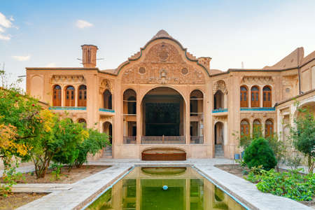 Wonderful view of traditional Iranian courtyard with garden and pool in the middle at the Borujerdi Historical House in Kashan, Iran. Gorgeous Persian architecture. Beautiful exterior. Publikacyjne