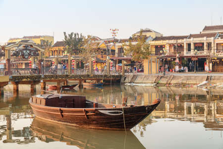 Hoi An (Hoian), Vietnam - April 12, 2018: Amazing view of traditional Vietnamese wooden boat on the Thu Bon River in Hoi An Ancient Town. Old yellow houses reflected in water. Awesome cityscape. Zdjęcie Seryjne - 125865873