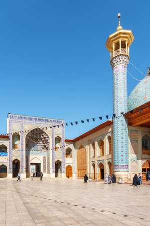 Shiraz, Iran - 29 October, 2018: Gorgeous view of courtyard and scenic gate of the Shah Cheragh Mosque and Mausoleum. Awesome minaret is visible on blue sky background. Amazing Islamic architecture. Redakční