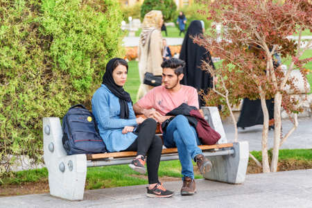 Isfahan, Iran - 24 October, 2018: Young pretty Iranian couple resting in Naqsh-e Jahan Square. The square is a popular tourist attraction and recreational gathering place among residents. Zdjęcie Seryjne - 125865880