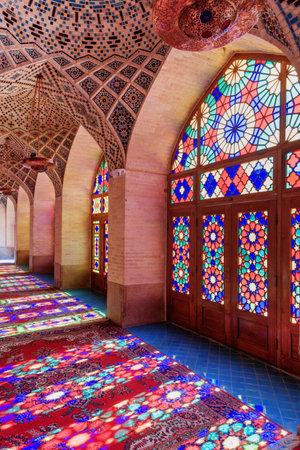 Schöne Aussicht auf die Morgensonne, die durch bunte Glasfenster auf dem Boden der Gebetshalle in der Nasir al-Mulk-Moschee (rosa Moschee) in Shiraz, Iran, reflektiert wird. Erstaunliches persisches Interieur. Editorial
