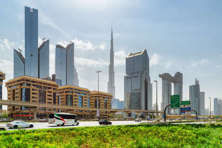 Dubai, United Arab Emirates - 2 November, 2018: Wonderful view of skyscrapers at downtown. The iconic Burj Khalifa Tower is visible on blue sky background. Day traffic of Sheikh Zayed Road. Zdjęcie Seryjne - 125865885