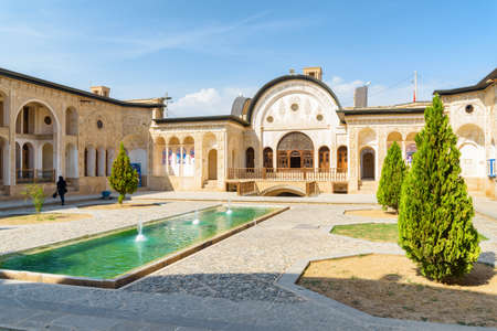Kashan, Iran - 21 October, 2018: Gorgeous view of traditional Iranian courtyard with pool and fountains in the middle at Tabatabaei Historical House. Wonderful Persian architecture. Beautiful exterior