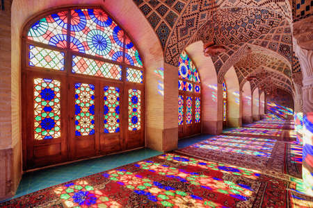 Awesome view of morning sunlight reflected through colorful stained glass windows on columns, the wall and the floor of prayer hall at the Nasir al-Mulk Mosque (Pink Mosque) in Shiraz, Iran. Zdjęcie Seryjne - 125865888