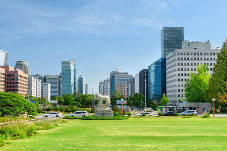 Seoul, South Korea - October 14, 2017: View of green lawn in front of the National Assembly Proceeding Hall at Yeouido (Yeoui Island). Skyscrapers and other modern buildings on blue sky background.