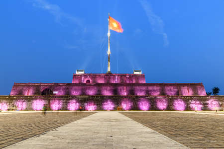 Night view of a square and the Flag Tower of the Citadel illuminated by pink lights in Hue, Vietnam. Within the Citadel is the Imperial City with the Purple Forbidden City. Zdjęcie Seryjne - 125865894