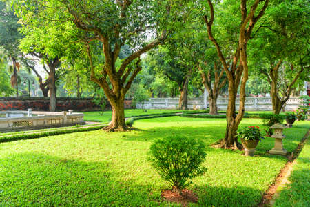 Awesome view of beautiful traditional Vietnamese garden at the Temple of Literature in Hanoi, Vietnam. Old trees and green grass. The Temple of Confucius is a popular tourist destination of Asia. Zdjęcie Seryjne