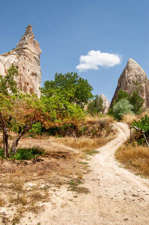Scenic pathway among Fairy Chimney Rock Formations in Goreme National Park at Cappadocia, Turkey. Awesome landscape. Cappadocia is a popular tourist destination of Turkey.