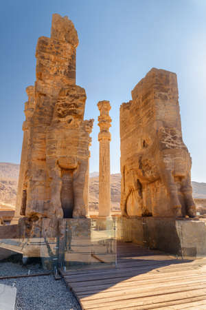 Scenic ruins of the Gate of All Nations on blue sky background in Persepolis, Iran. Ancient Persian city. Persepolis is a popular tourist destination of the Middle East.