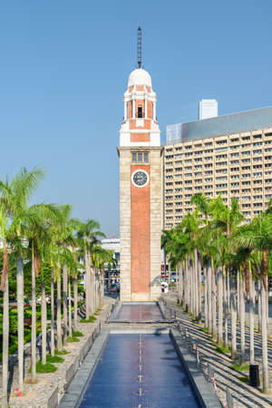 Wonderful view of the Clock Tower (Former Kowloon-Canton Railway Clock Tower) in Tsim Sha Tsui of Hong Kong. Awesome cityscape on sunny day. Hong Kong is a popular tourist destination of Asia.