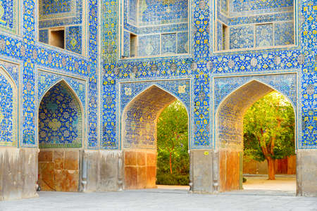 Isfahan, Iran - 23 October, 2018: Amazing arches covered with colorful mosaic tiles at courtyard of the Shah Mosque (Imam Mosque). Awesome Persian exterior of the Muslim place. Islamic architecture.
