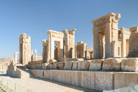 Amazing ruins of the Tachara Palace on blue sky background in Persepolis, Iran. Scenic view of the most intact of all ruins at the ceremonial capital of the Achaemenid Empire. Ancient Persian city.
