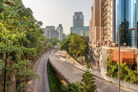 Awesome morning view of Kowloon Park Drive in Tsim Sha Tsui of Hong Kong. Scenic empty road. Unusual cityscape. Hong Kong is a popular tourist destination of Asia.