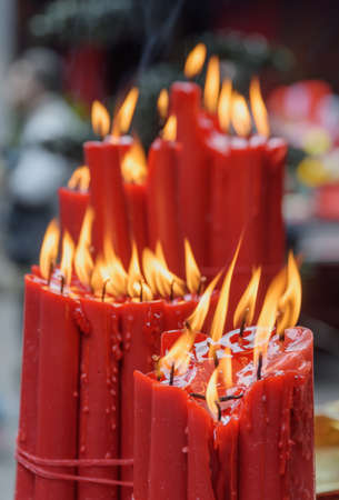 Awesome closeup view of burning red ritual candles in a Buddhist temple.