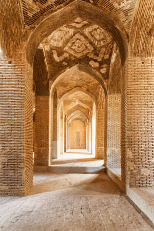 Isfahan, Iran - 23 October, 2018: Amazing vaulted arch passageway among columns inside the Jameh Mosque of Isfahan. The Muslim place is a popular tourist attraction of the Middle East.
