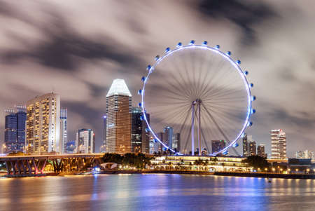 Singapore - February 18, 2017: Awesome night view of the Singapore Flyer and Marina Bay. Amazing colorful cityscape. The giant observation wheel is a popular tourist attraction of Asia.