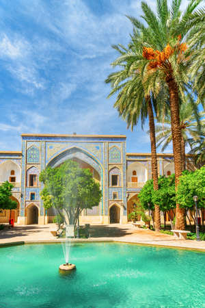 Wonderful fountain in the middle of traditional Persian courtyard with green garden at Madrese e-Khan in Shiraz, Iran. The ancient religious school is a popular tourist attraction of the Middle East.