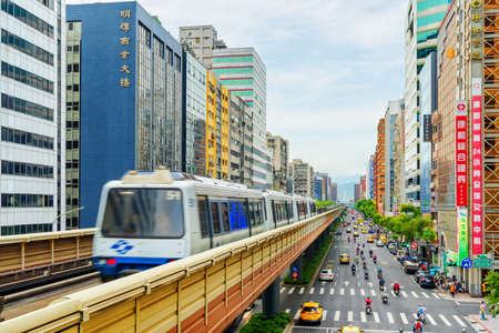 Taipei, Taiwan - April 26, 2019: View of train of the Taipei Metro passing above Fuxing Road. Viaduct of Wenhu line. Day traffic. Awesome cityscape. Taipei is a popular tourist destination of Asia. Publikacyjne