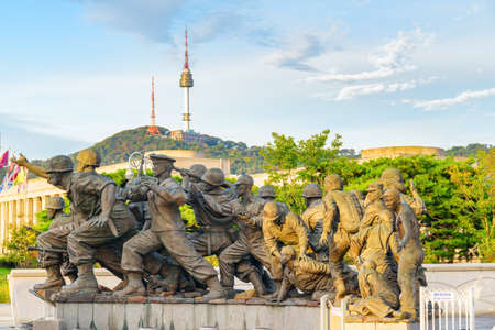 Seoul, South Korea - October 14, 2017: View of sculptures of the Korean War Monument. The War Memorial of Korea is a popular tourist attraction of Asia. Namsan Seoul Tower is visible in background.