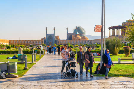 Isfahan, Iran - 23 October, 2018: Iranian families resting and walking along Naqsh-e Jahan Square. The Shah Mosque (Imam Mosque) and the Ali Qapu Palace are visible on blue sky background.