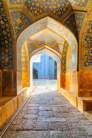 Isfahan, Iran - 23 October, 2018: Scenic vaulted arch corridor leading to courtyard of the Shah Mosque (Imam Mosque). Amazing Persian interior of the Muslim place. Beautiful Islamic architecture.