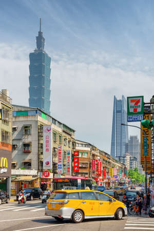 Taipei, Taiwan - April 25, 2019: Awesome view of Songren Road on sunny day. Taipei 101 (Taipei World Financial Center) and other skyscrapers are visible on blue sky background. Scenic cityscape. Publikacyjne