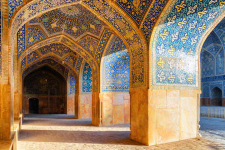 Isfahan, Iran - 23 October, 2018: Awesome vaulted arch passageway at the Shah Mosque (Imam Mosque). Amazing Persian interior of the Muslim place. Colorful mosaic tiles. Islamic architecture. Publikacyjne