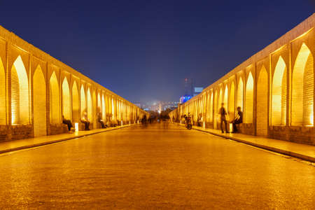 Night view of walkway on the Allahverdi Khan Bridge (Si-o-se-pol) in Isfahan, Iran. The vaulted arch bridge is a popular recreational gathering place among Iranian young people.