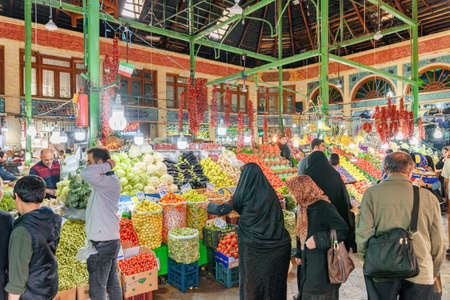 Tehran, Iran - 18 October, 2018: Wide range of fresh vegetables at Tajrish Bazaar. Iranian women wearing black chadors. The historical market is a popular tourist destination of the Middle East. Publikacyjne