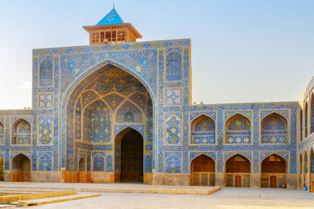Scenic courtyard of the Shah Mosque (Imam Mosque) in Isfahan, Iran. Walls covered with colorful mosaic tiles. Awesome Persian exterior of the Muslim place. Amazing Islamic architecture.