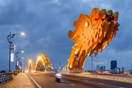 Awesome evening view of the Dragon Bridge (Cau Rong) over the Han River at downtown of Da Nang (Danang), Vietnam. Beautiful cityscape. The Dragon Bridge is a popular tourist attraction of Asia.