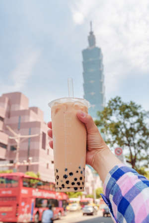 Closeup view of female hand holding traditional Taiwanese bubble milk tea in downtown of Taipei, Taiwan. Skyscraper is visible in background. The pearl tea is a popular drink with chewy tapioca balls.