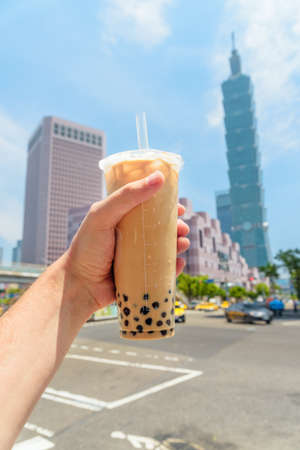 Closeup view of male hand holding traditional Taiwanese bubble milk tea in downtown of Taipei, Taiwan. Skyscraper is visible in background. The pearl tea is a popular drink with chewy tapioca balls.