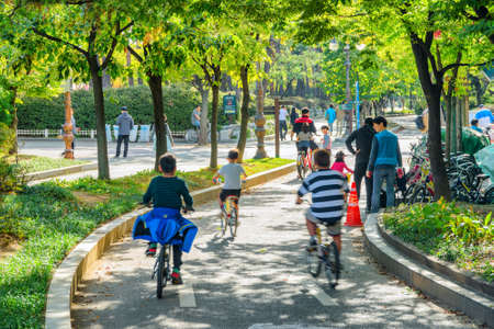 Seoul, South Korea - October 14, 2017: Korean families resting and walking along scenic green park. Children bicycling among trees. The park is a popular recreational gathering place among residents.