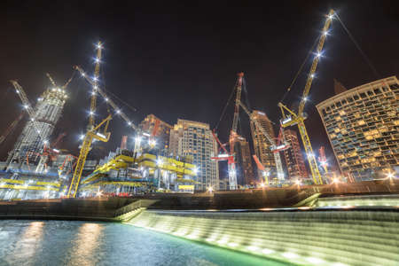 Dubai, United Arab Emirates - 2 November, 2018: Amazing night view of scenic waterfall and under construction skyscrapers at downtown. Dubai is a popular tourist destination of UAE.