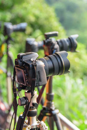 Taipei, Taiwan - April 25, 2019: View of row of professional cameras on tripods among green trees. Scenic spot for photo. Photographers taking pictures. Focus on the first camera. 스톡 콘텐츠