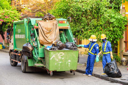 Hoi An (Hoian), Vietnam - April 12, 2018: Two garbagemen loading trash by hand. Garbage truck at old street of Hoi An Ancient Town in morning. Hoian is a popular tourist destination of Asia.