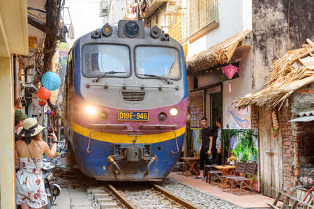 Hanoi, Vietnam - April 18, 2019: Closeup view of train passing through a narrow street of the Hanoi Old Quarter. Tourists taking pictures of the train. The Hanoi Train Street is a popular attraction.