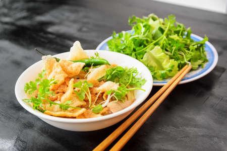 Cao Lau sur table en bois noir du café de la rue à Hoi An (Hoian) dans la province de Quang Nam au centre du Vietnam. Le Cao Lau est un plat vietnamien régional à base de nouilles, de porc et de légumes verts locaux.