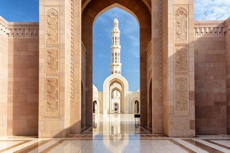 Amazing view of minaret through scenic arches of the Sultan Qaboos Grand Mosque in Muscat, Oman. Beautiful Islamic architecture. The Muslim place is a popular tourist attraction of the Middle East.
