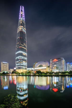 Wonderful night view of skyscraper and other modern buildings reflected in lake at downtown of Seoul in South Korea. Amazing cityscape. Seoul is a popular tourist destination of Asia.