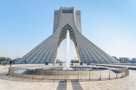 Scenic view of the Azadi Tower (Freedom Tower) on blue sky background and fountain on Azadi Square in Tehran, Iran. Tehran is a popular tourist destination of the Middle East.