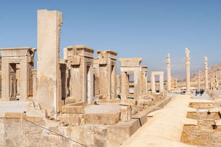 Ruins of the Tachara Palace and columns of the Apadana Palace on blue sky background in Persepolis, Iran. Ancient Persian city. Persepolis is a popular tourist destination of the Middle East.