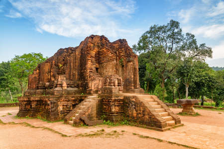 Beautiful view of red brick temple of My Son Sanctuary among green woods in Da Nang (Danang), Vietnam. My Son is a complex of partially ruined ancient Hindu temples constructed by the kings of Champa. Stock Photo