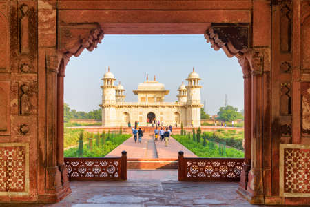 Agra, India - 9 November, 2018: Unusual view of the Tomb of Itimad-ud-Daulah (Baby Taj) through red sandstone gate. The white marble mausoleum is a popular tourist attraction of South Asia.