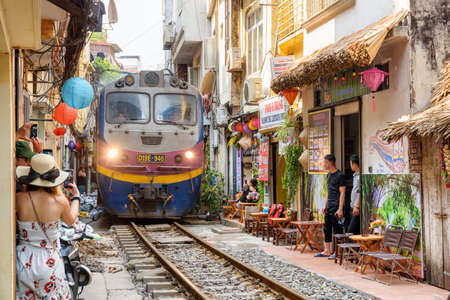 Hanoi, Vietnam - April 18, 2019: Incredible view of train passing through a narrow street, the Hanoi Old Quarter. Tourists taking pictures of the train. The Hanoi Train Street is a popular attraction. Stock Photo