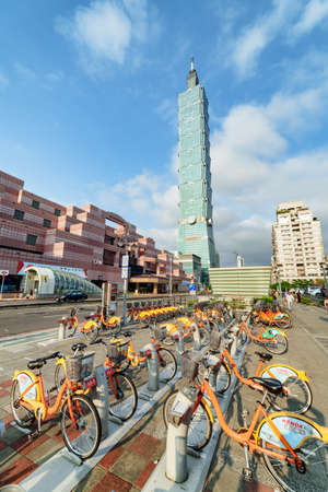 Taipei, Taiwan - April 26, 2019: Bicycle parking station of the Taipei Bike Sharing System. Scenic view of Taipei 101 and orange YouBikes on Xinyi Road at downtown. Fabulous cityscape.