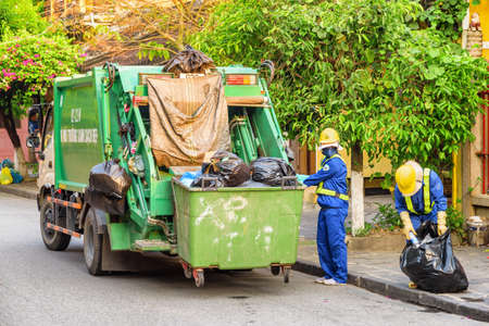 Hoi An (Hoian), Vietnam - April 12, 2018: Garbage collectors loading trash by hand. Garbage truck at old street of Hoi An Ancient Town in morning. Hoian is a popular tourist destination of Asia.