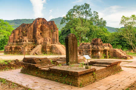 Awesome view of stone slab with Sanskrit inscriptions and ruins of My Son Sanctuary, Da Nang, Vietnam. My Son is a complex of partially ruined ancient Hindu temples constructed by the kings of Champa.